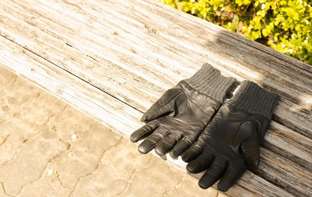 A pair of leather gloves drying in the sun.