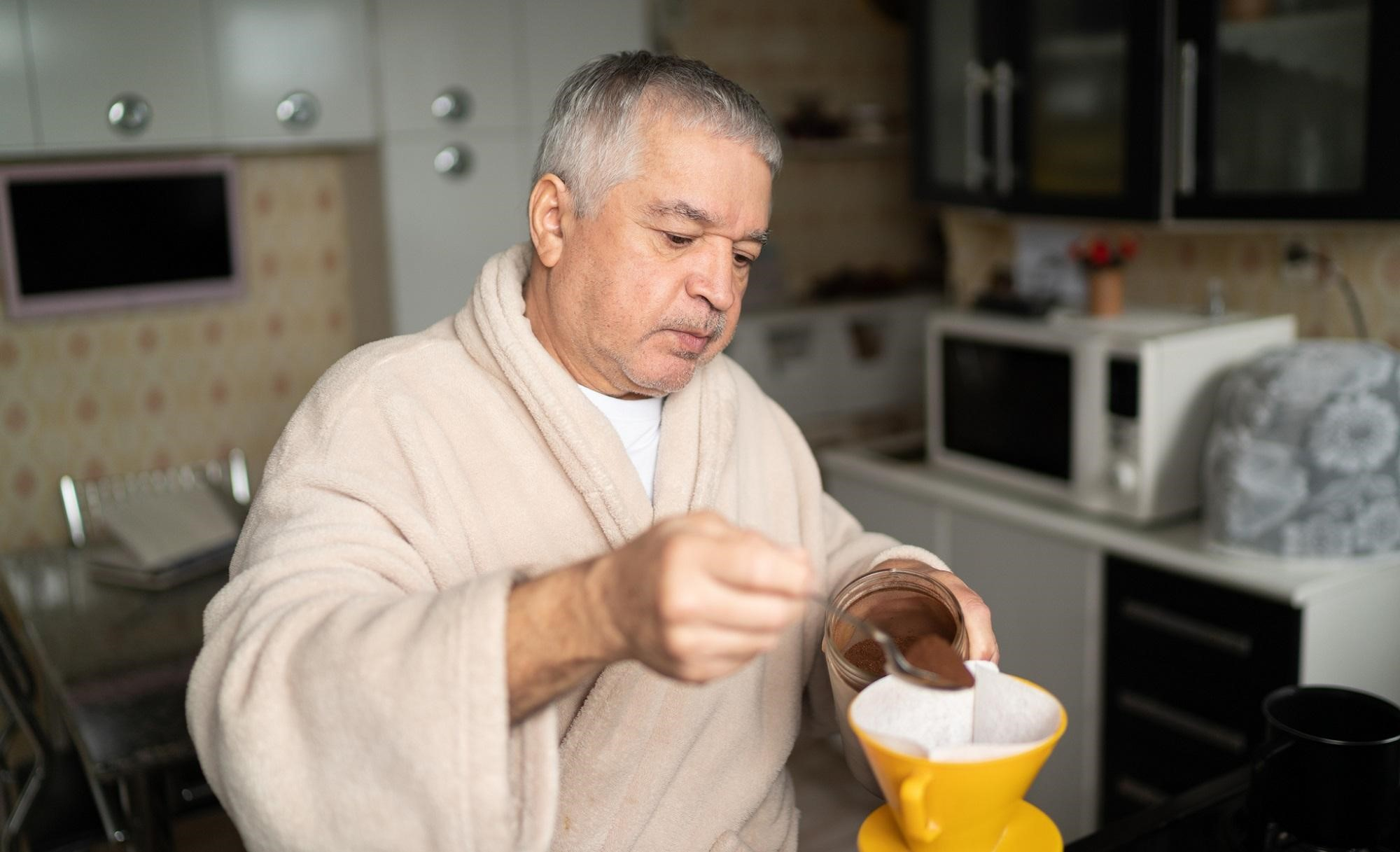 An older man in a bathrobe making coffee.