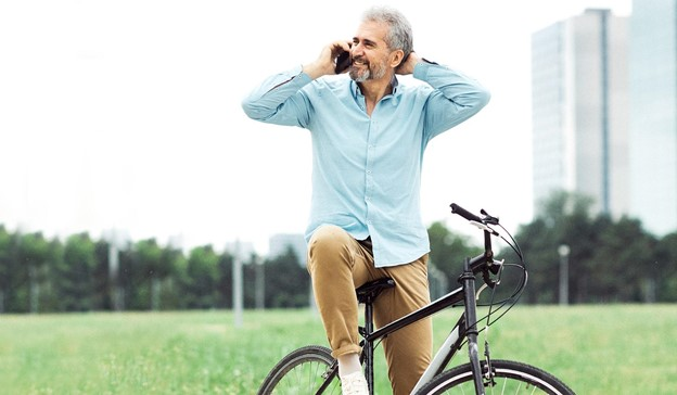 An older man wearing chinos and a shirt on a bike