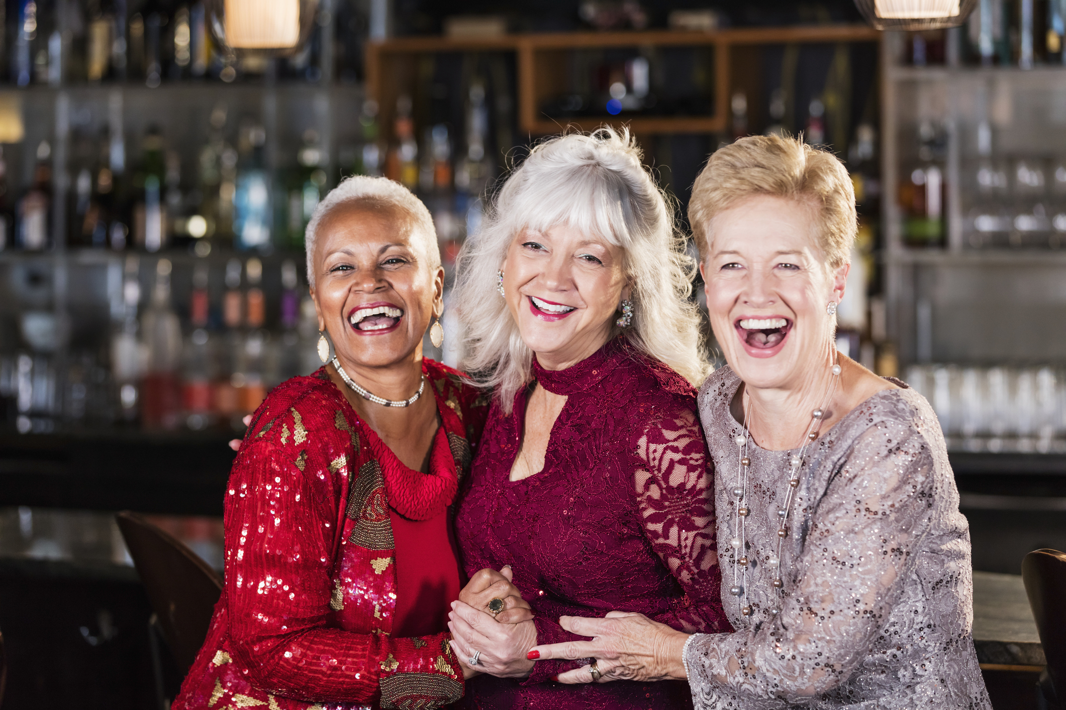 Three older women laughing dressed in cocktail attire in a bar.