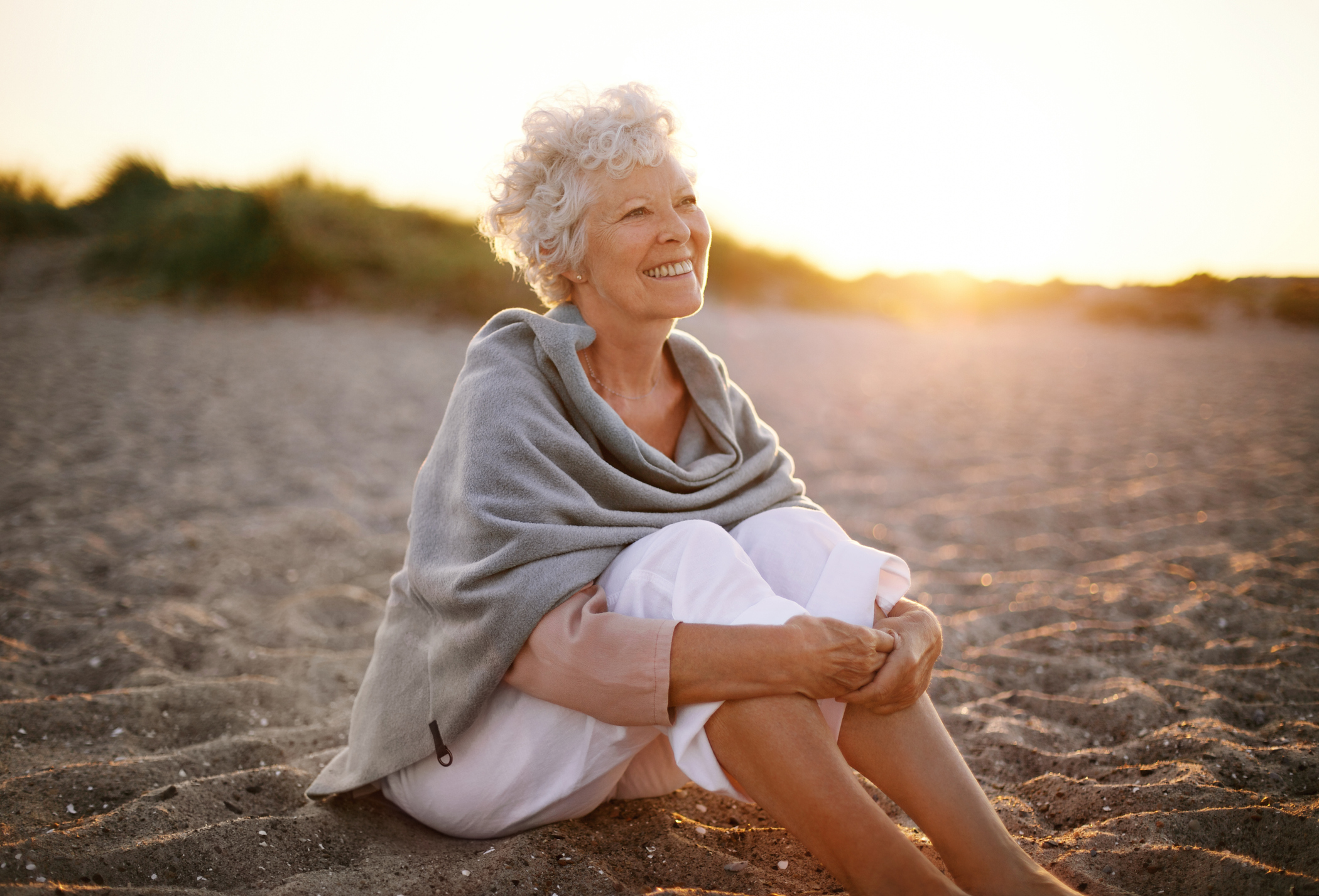Older woman sitting on a beach wearing cropped white trousers