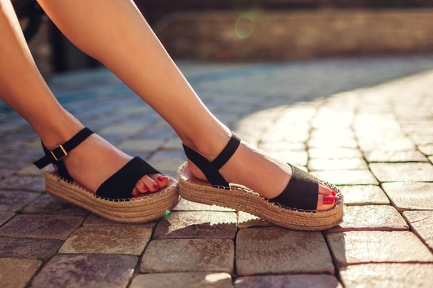 Stylish woman wearing black summer sandals with straw soles.