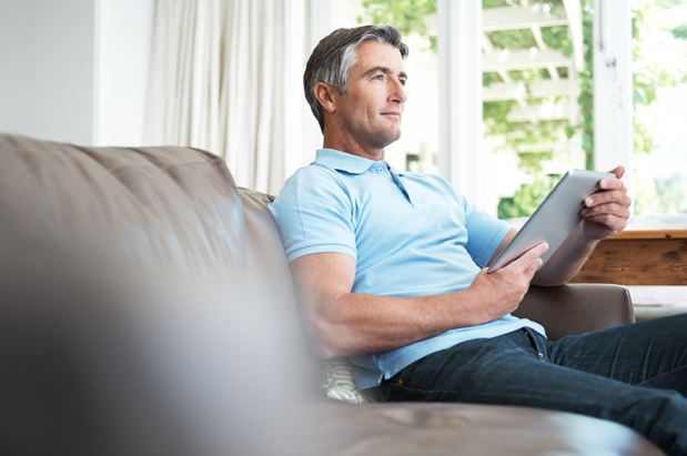 Older man wearing a blue polo shirt relaxing on the sofa
