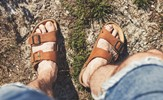 an older man wearing leather sandals.