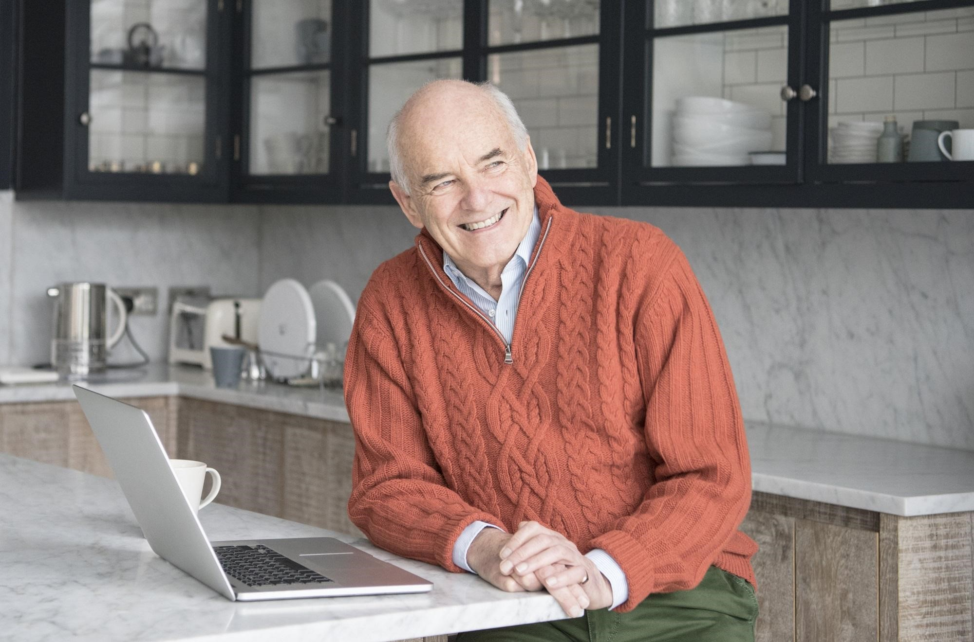 An older man wearing a sweater in the kitchen