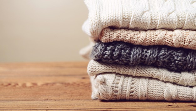 A set of knitted jumpers piled up on a table.