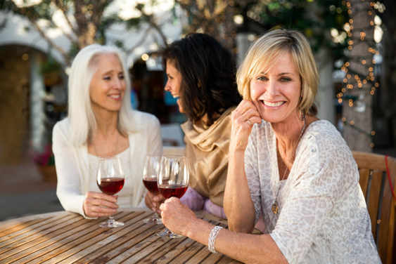 Image alt text: mature woman in a patterned blouse drinking wine with her friends