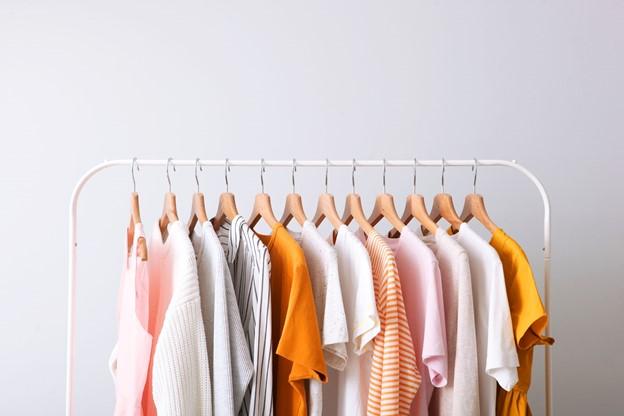 light coloured clothing hanging on rail against white background