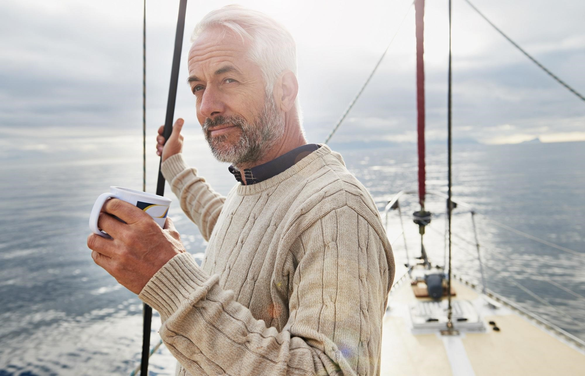 An older man wearing a sweater on a boat