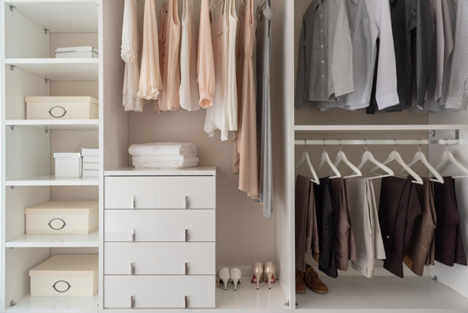 a large built in wardrobe with pastel-coloured women's clothes on one side and grey and brown men's clothes on the other